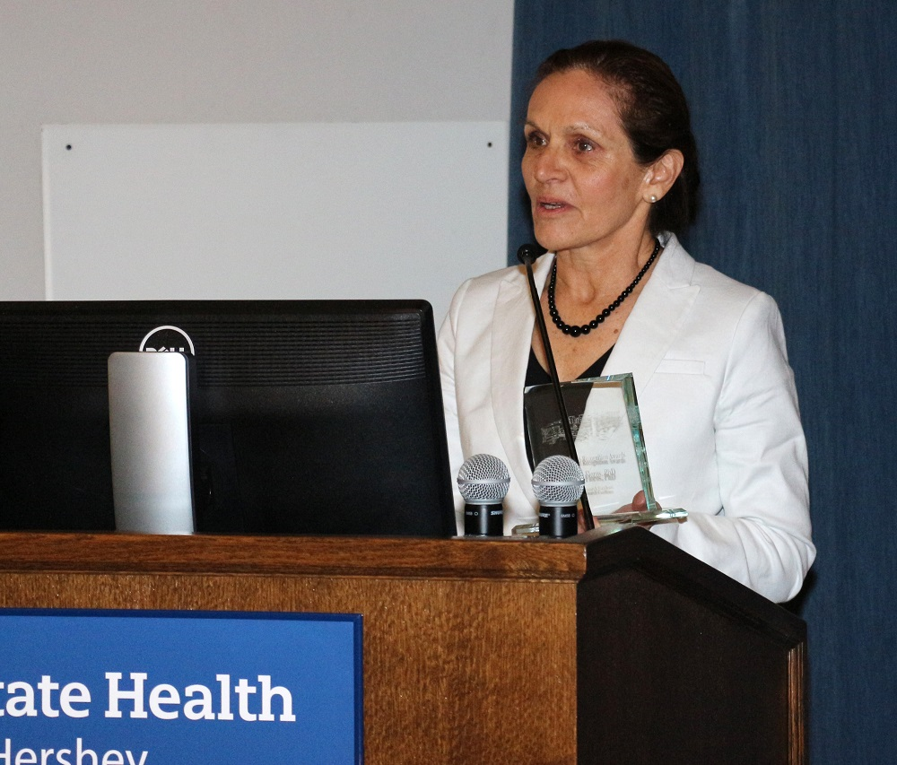 Joanna Floros, wearing a white coat and holding a glass award, speaks at a lectern.