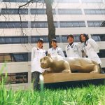 Four senior medical students from Tokyo Women's Medical University stand behind the Penn State Nittany Lion in front of Penn State College of Medicine.