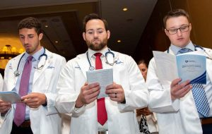 Eric Burfeind, Bradley Brockbank and Morgan Bensiger, each wearing white coats with stethoscopes draped around their necks, stand in a row and read from pamphlets.