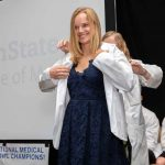 Kerri Schopf, wearing a dress, smiles as another woman stands behind her and slips a white coat onto her shoulders. Behind her, the words Penn State College of Medicine are projected onto a screen.