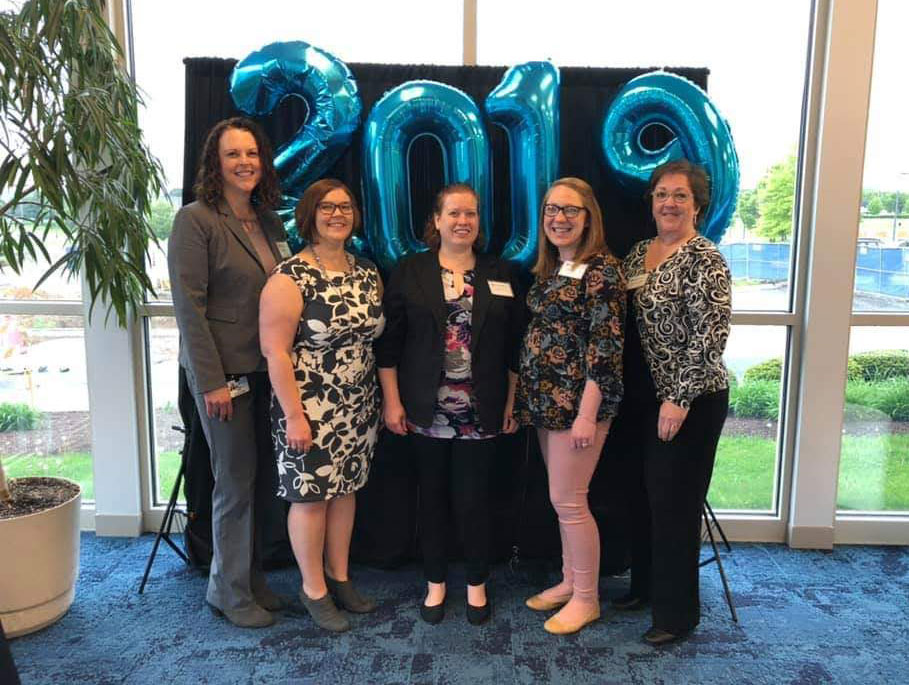 Five women are pictured standing in a lobby in front of individual balloons with the numbers 2-0-1-9 on them visible behind their heads.