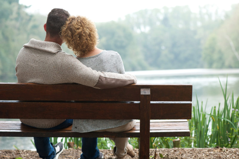A man and a woman sit side by side on a wooden bench, facing away from the camera. The man's arm is around the woman. They look out at a lake surrounded by trees.