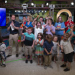 "Several people -- more than a dozen children and two adults -- share space on a TV set. The Children's Miracle Network logo is in the background on the right; a TV monitor with the figure ""$4,445,580"" is on the left."