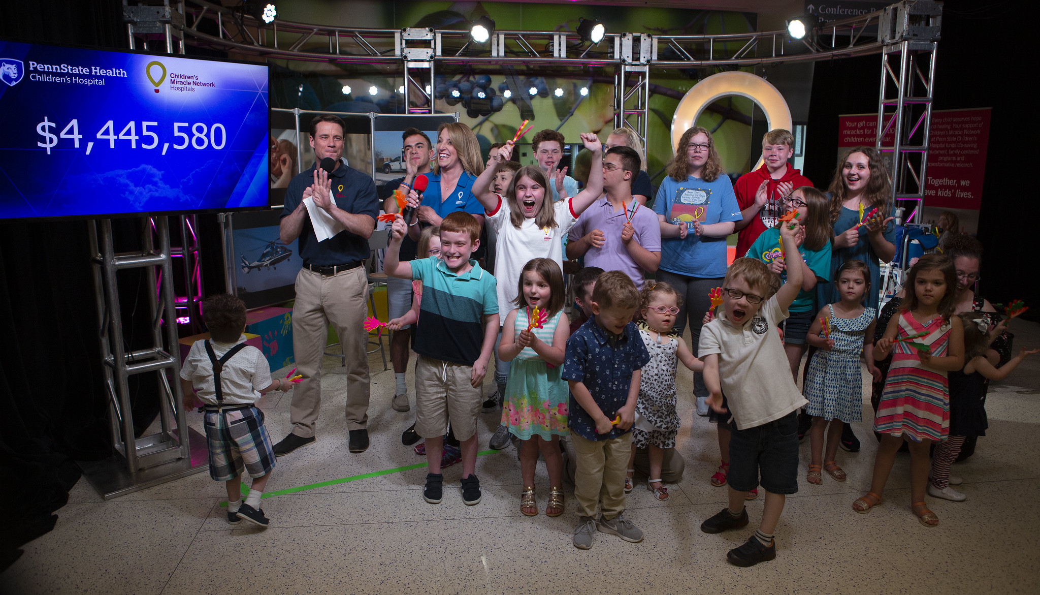 Several people -- more than a dozen children and two adults -- share space on a TV set. The Children's Miracle Network logo is in the background on the right; a TV monitor with the figure