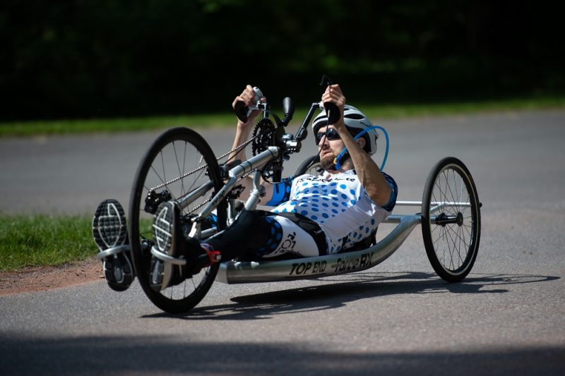 Cody Wills, wearing a helmet and sunglasses, rides his hand cycle, lying on his back, his fists grip handles that that push the bike forward on three wheels.