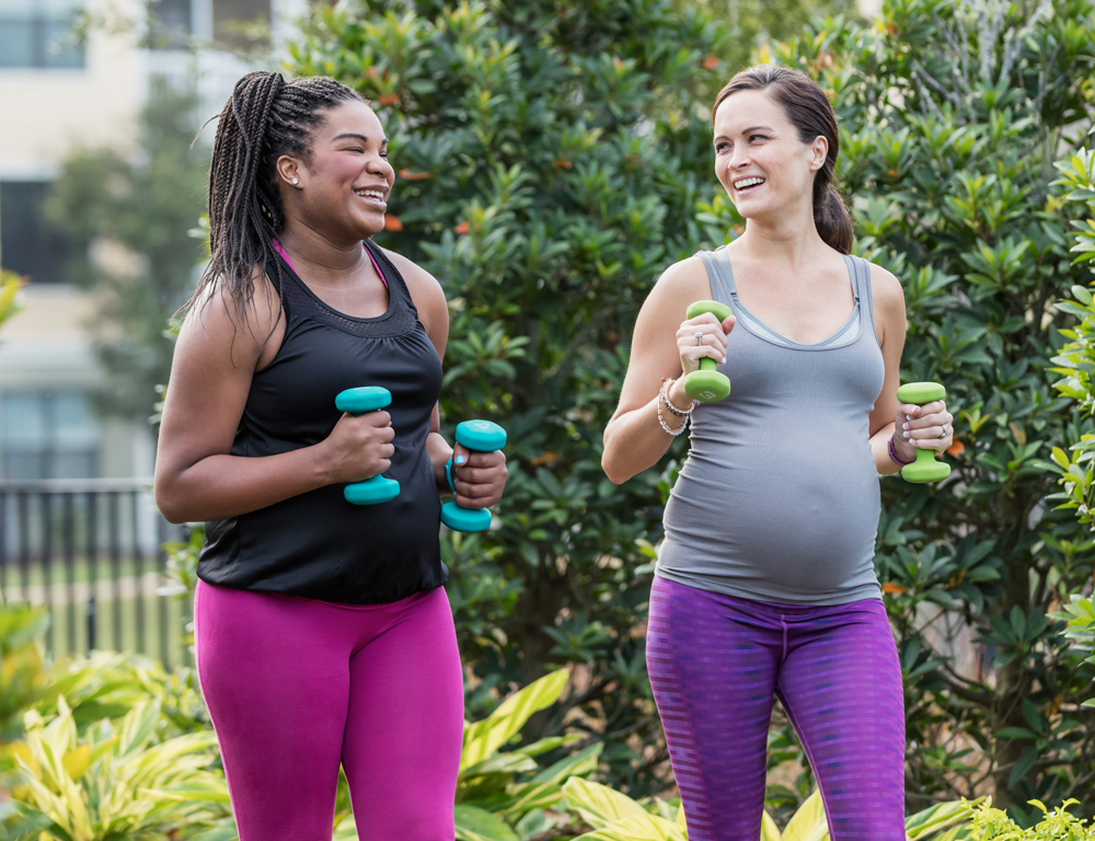 Two women in exercise clothing walk side-by-side, each holding small hand weights. They look at each other, smiling. Bushes are in the near background; farther in the background is an apartment building, slightly out of focus.