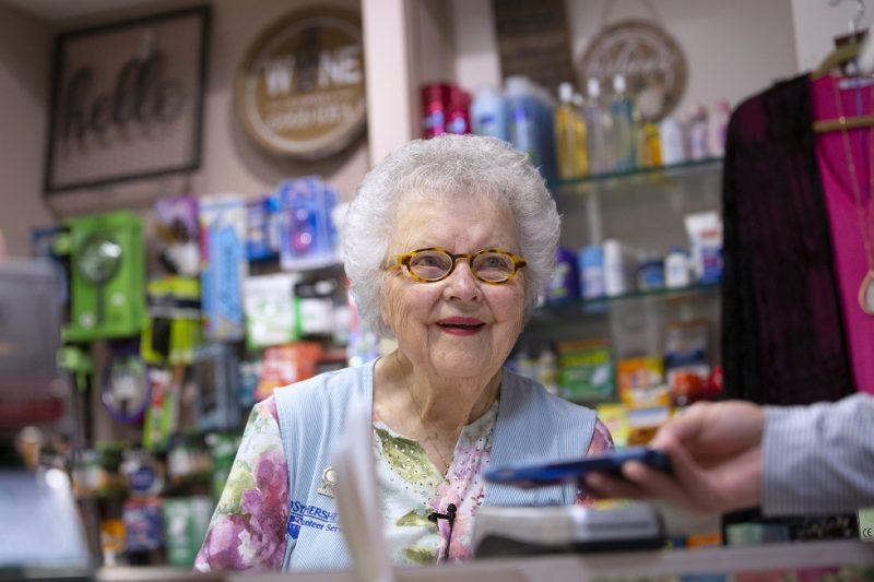 Arlene Faul, a 95-year-old woman from Hershey, smiles behind the counter of the Hershey Medical Center gift shop. She is wearing a vest, shirt, necklace and glasses. A man's hand holds a phone out to her. Behind her are shelves of toiletries and other items. A top and sweater hang on a hanger on the right.