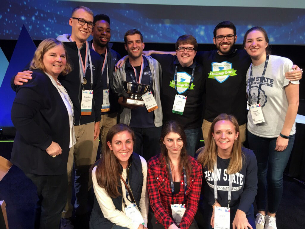 Members of Penn State College of Medicine's physician assistant program National Challenge Bowl team and program alumni and leadership are seen kneeling and standing in a group.