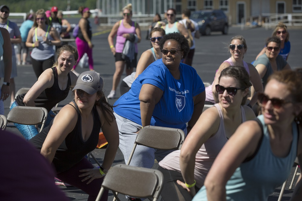 Meghan Culpepper, wearing sunglasses and a Penn State Health T-shirt, joins a group of women all in the same workout position staring at something to the left of the frame.
