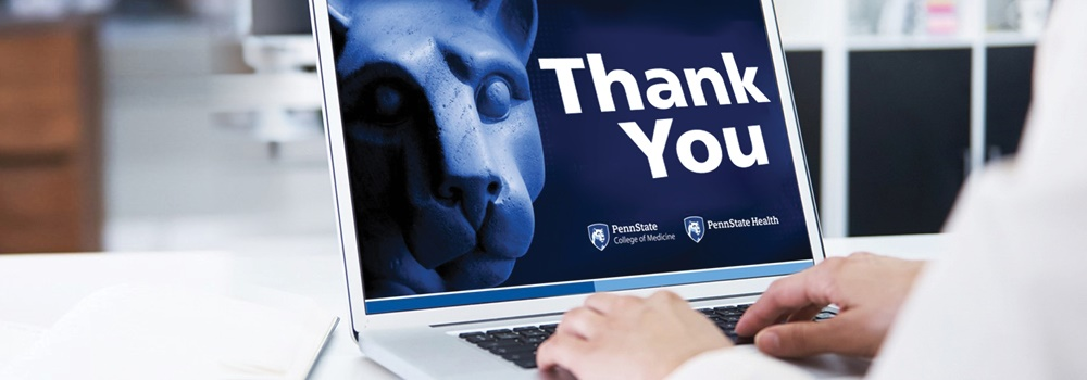 Hands can be seen typing at a laptop keyboard. On the screen is an image of the Penn State Nittany Lion statue and the words Thank You.