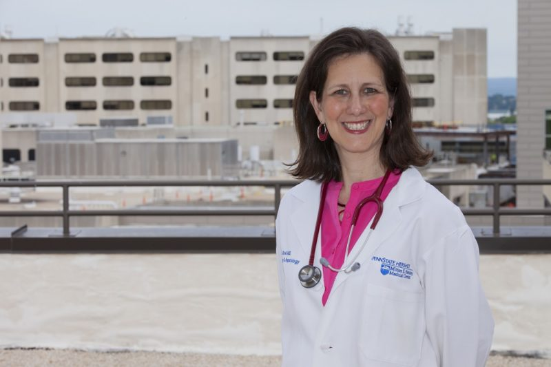 Dr. Karen Krok stands on the roof of Penn State College of Medicine smiling and wearing a white lab coat and stethoscope around her neck. The Hershey Medical Center logo is on the right pocket of her lab coat. She has medium-length brown hair. Behind her a building is under construction.
