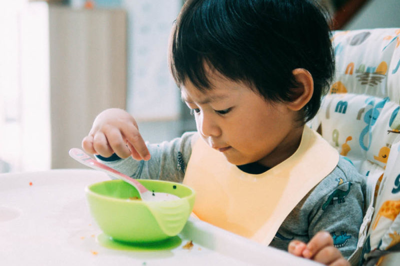 A young child sits at a table with a bowl and a spoon.
