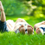 Three young people lay side by side in a grassy area. The photo is taken from the ground, viewing their feet. The person on the left has their feet raised into the air. A line of trees is in the background, out of focus.