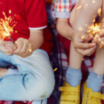 Two children hold sparklers in their hands.