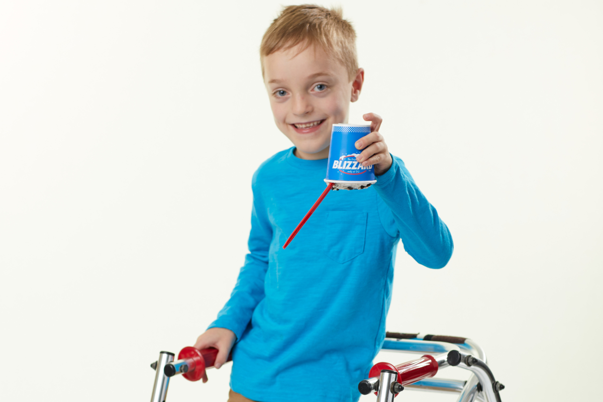A boy smiles for a photo while holding a cup of ice cream