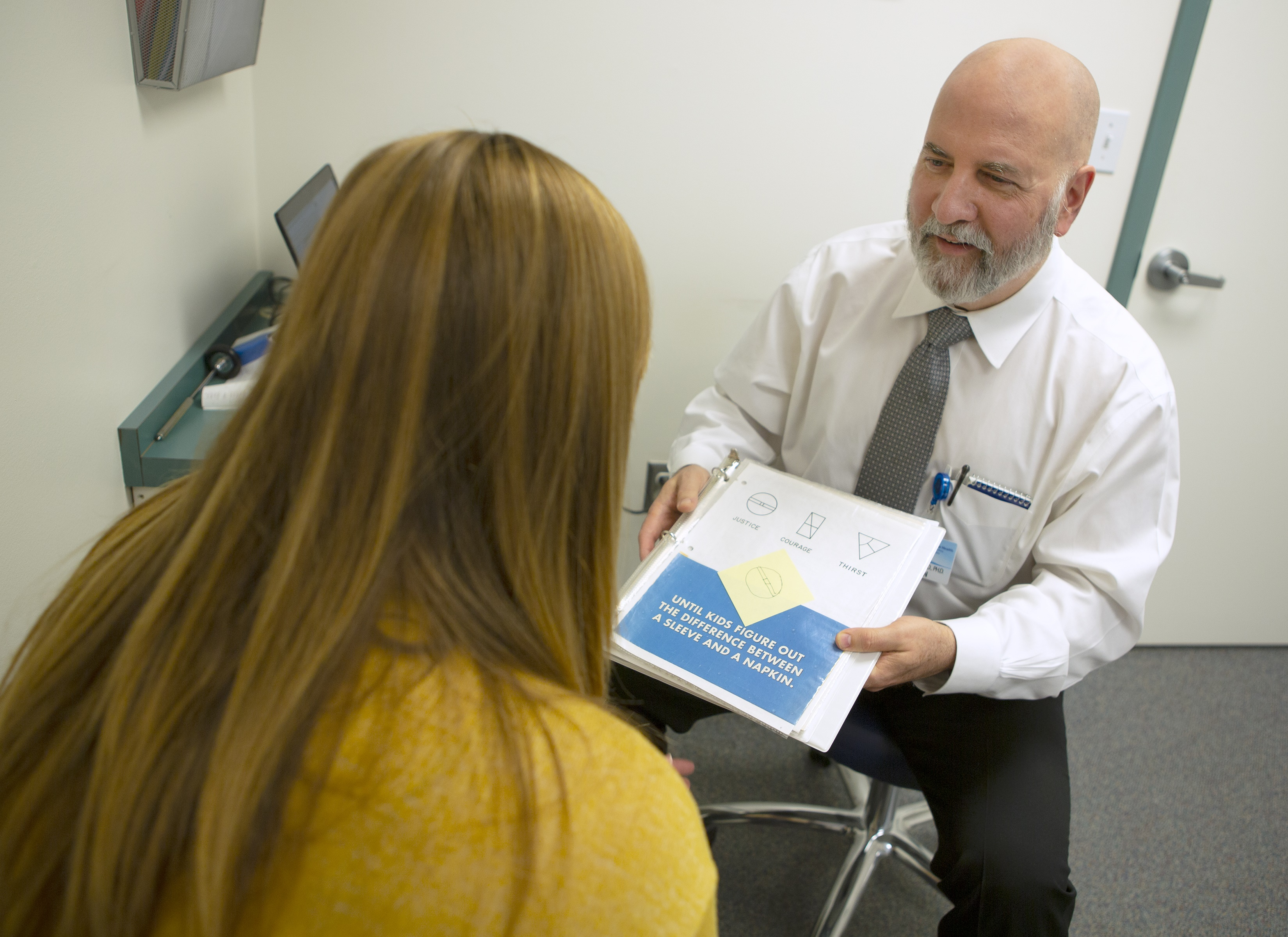 A male physician wearing a tie sits on a stool in an exam room, displaying a page with various diagrams on it to a female patient who sits across from him.
