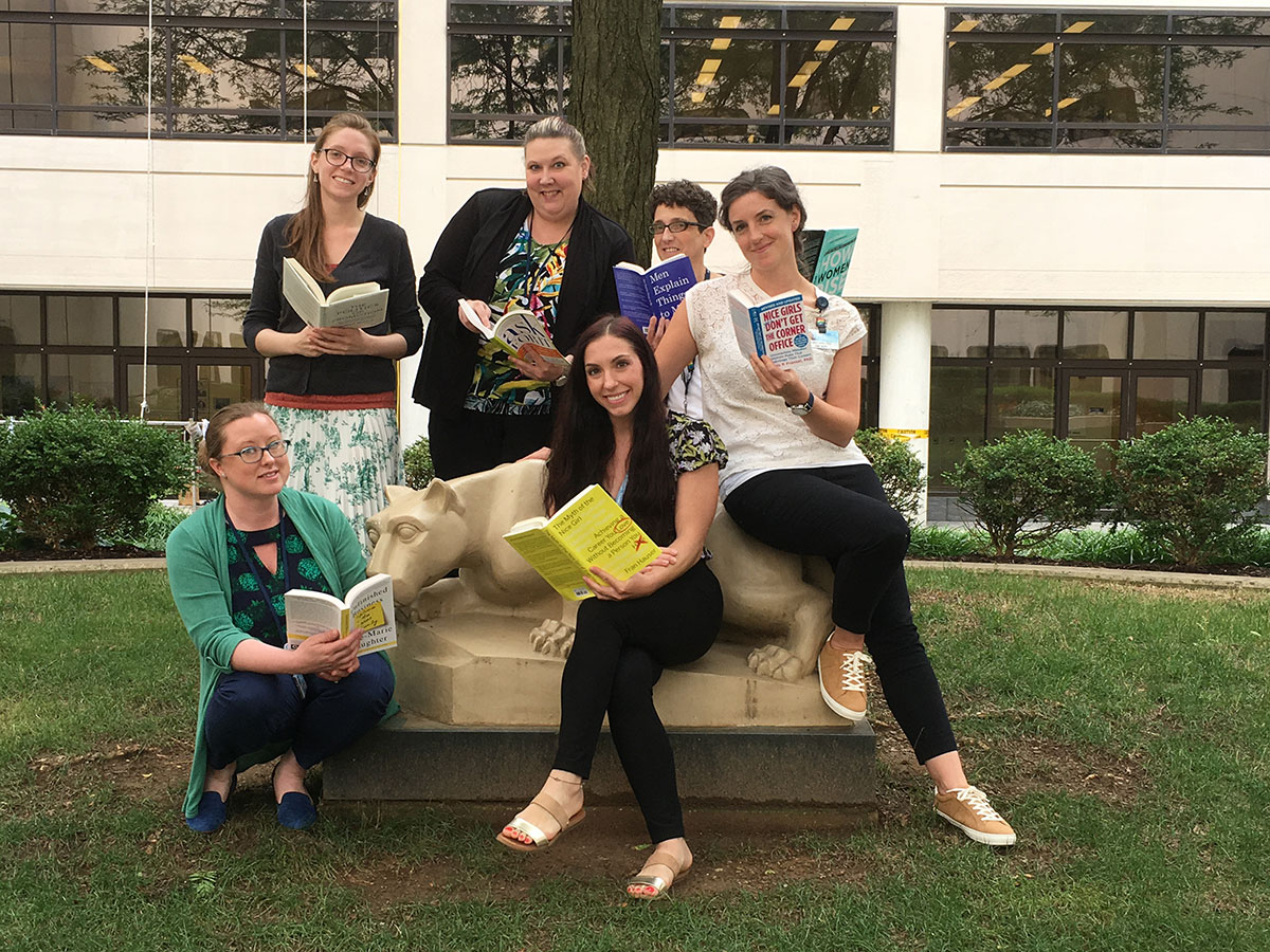 A group of six women are pictured sitting on and standing near a statue of the Penn State Nittany Lion in an outdoor courtyard. Each woman is holding a book.