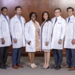 Six men and women in lab coats smile at the camera as they stand in front of a wood wall.