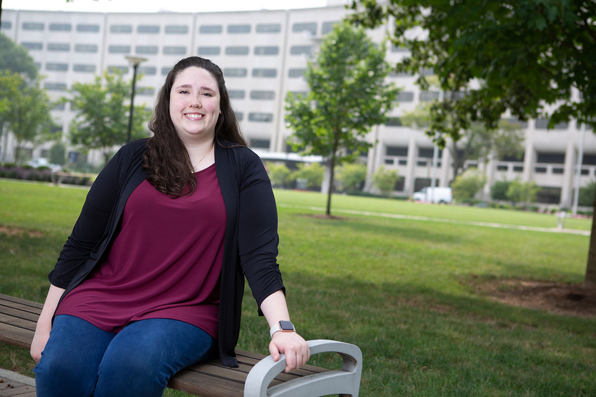 Alissa Meister sits on a bench on the lawn of Penn State College of Medicine, which is seen in the background.
