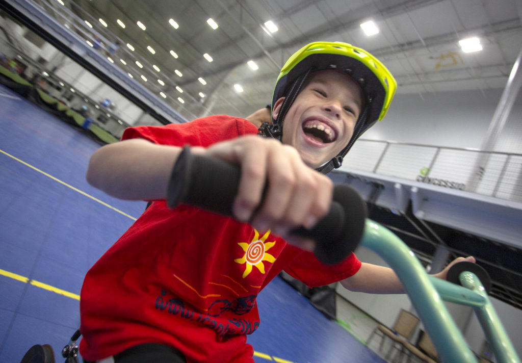 Owen Zeager, 8, smiles as he rides his bike at the iCan Bike Camp at Spooky Nook Sports Complex. He is wearing a T-shirt with a sun on it and a helmet. Behind him is a gym floor, a balcony and lights in the ceiling.