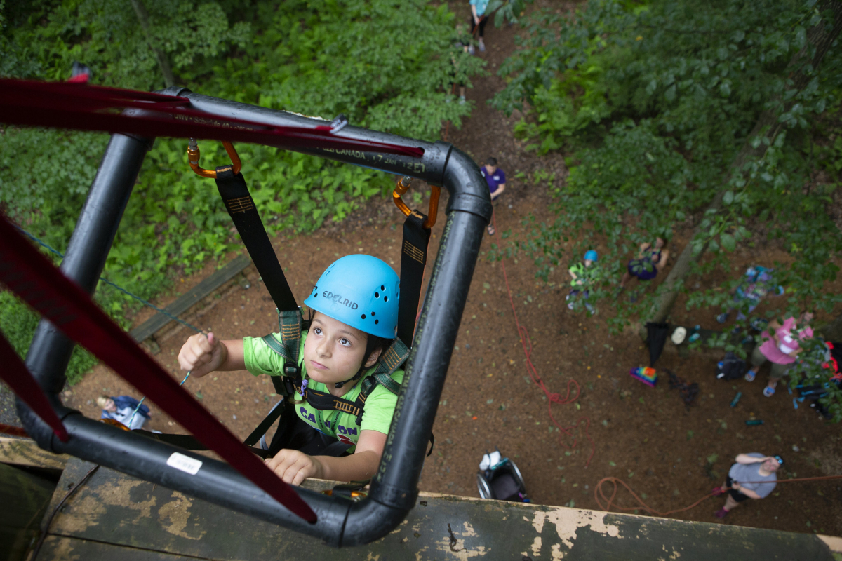 View from the top of a rock wall, looking down, as a young girl in climbing gear and supported by a square metal frame climbs the wall. About 6 people are on the ground, looking up.