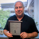 Dr. Robert Levenson of Penn State College of Medicine is seen in front of a window, holding a plaque.