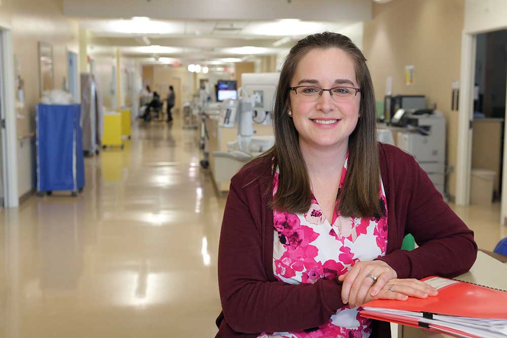Mary Codi, a medical social worker at Penn State Health St. Joseph, stands in a hallway at St. Joseph Medical Center. She is leaning on a table and has an orange folder in front of her. She is wearing glasses, a sweater and a flowered top. She has medium-length straight hair. Behind her hospital equipment and rooms are visible.