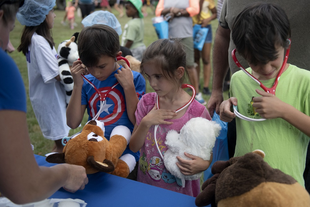 Three children stand in a row and wear stethoscopes. Two of the children hold stuffed animals .