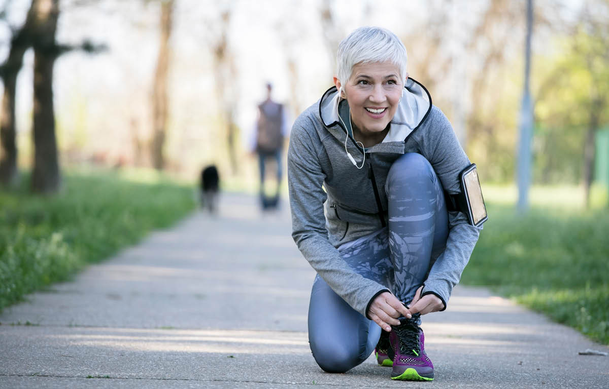 A woman in running tights and a light jacket kneels to tie her left shoe. She is on a paved walking path bordered by grass, and a person and dog are in the background, out of focus. A smart phone is strapped to the woman's left arm, and she has ear buds in.