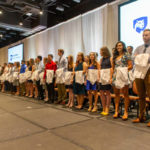 Several dozen medical students stand in two rows across a stage, with white medical coats draped over their left arms. The Penn State College of Medicine logo is projected on two screens behind them, and just in front of a pipe-and-drape backdrop.