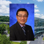 A head-and-shoulders professional photo of Duanping Liao is seen superimposed on an aerial photo of the campus of Penn State Health Milton S. Hershey Medical Center and Penn State College of Medicine in Hershey.