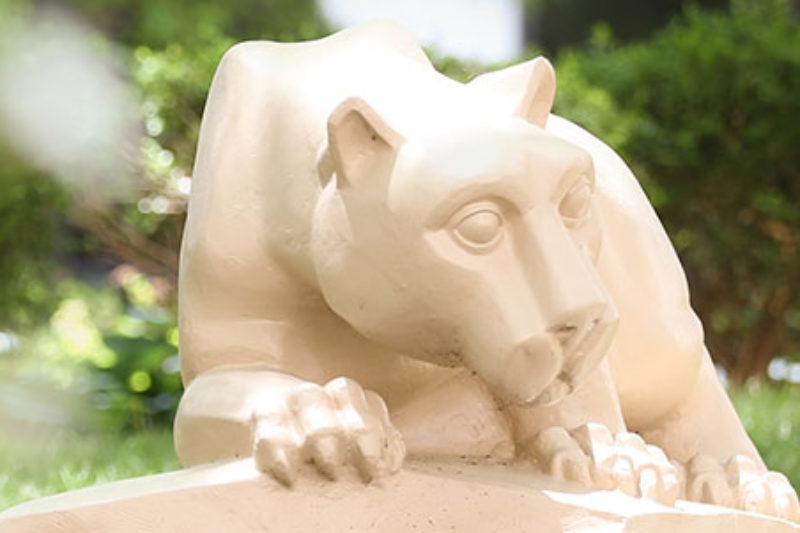 A statue depicting the mascot of Penn State University, the Nittany Lion, surrounded by bushes.