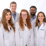 A group of seven college students are seen wearing white medical coats against a professional photo backdrop.