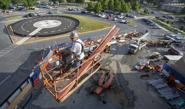 A man on construction equipment overlooks construction on the campus of a health system