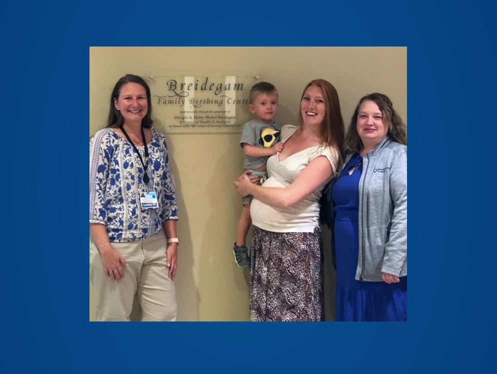 From left, Kimberly Hunter, St. Joseph OB nurse navigator, stands and smiles next to Kelsey Seyler who is holding her two-yer-old son and Sabrina Turner, certified nurse midwife, next to the Breidgam Family Birthing Center sign.