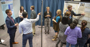 A group of researchers is seen standing around a set of academic posters. Smaller groups are in discussion with one another.
