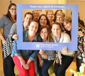 "Child Life team at Penn State Children's Hospital posing inside a frame to have their picture taken that says ""Thank you, Spirit of Children"""