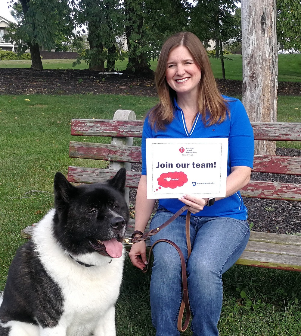 "Deborah Berini sits on a bench holding her dog Alvin's leash and a sign that says ""Join our team!"" She is wearing a polo shirt and jeans and has shoulder-length hair. Her dog is large and has black and white fur. Behind them are trees and grass."