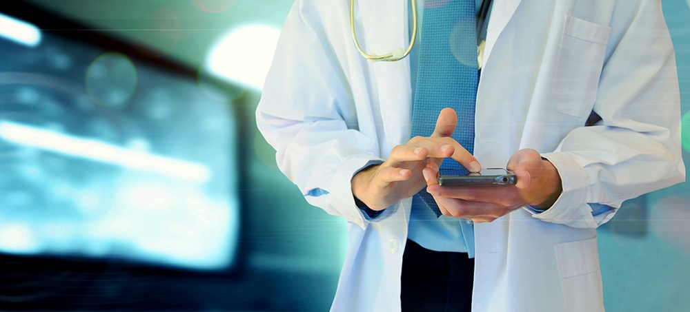 A male physician in a white lab coat touches the screen of a smartphone. He has a stethoscope over his shoulder. Behind him on the left is a monitor with an abstract image on it.