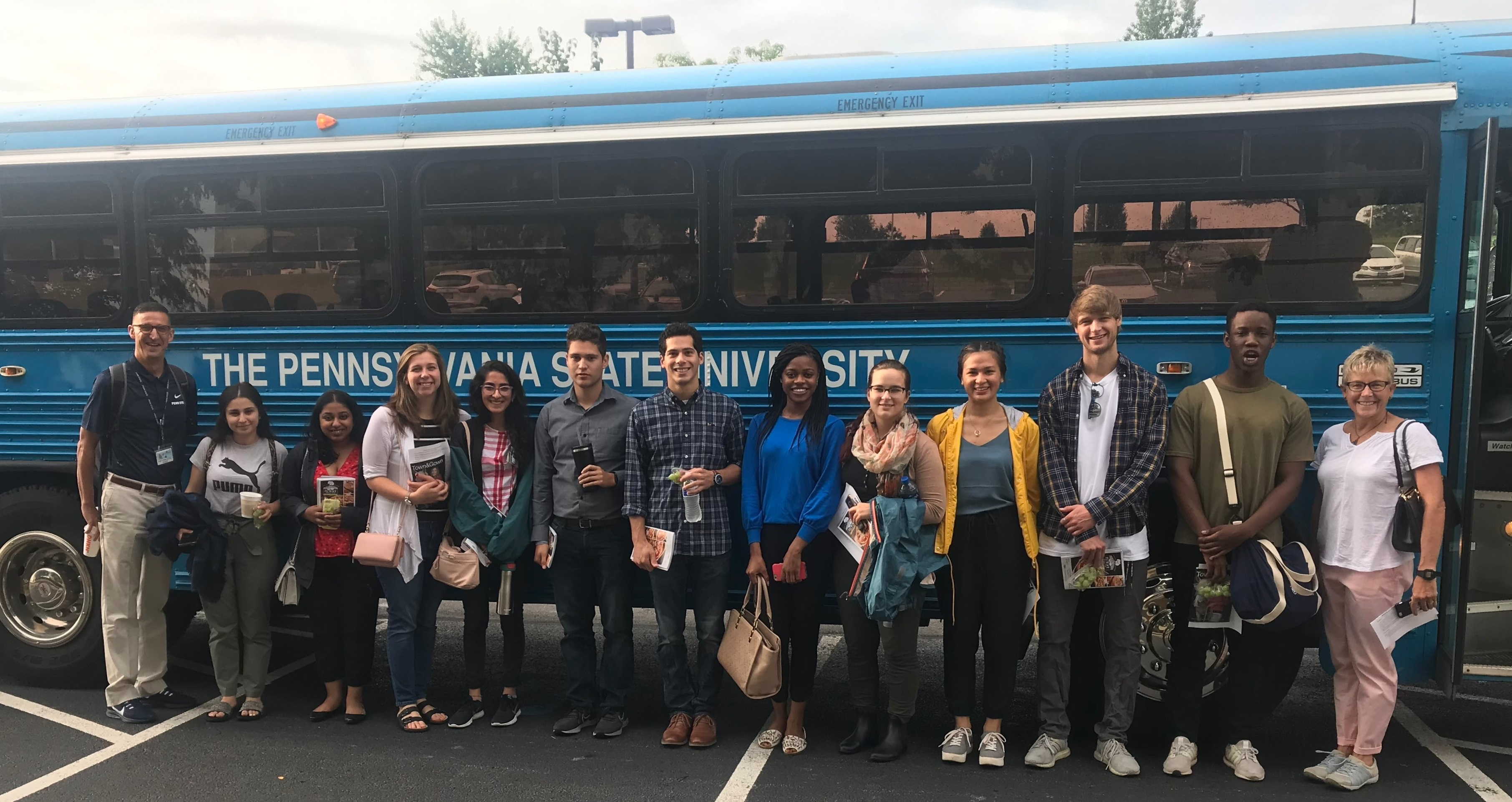 "Thirteen people dressed casually stand in a row in front of a bus that has a sign ""The Pennsylvania State University"" on it. A male professor on the left is wearing a lanyard and name badge."