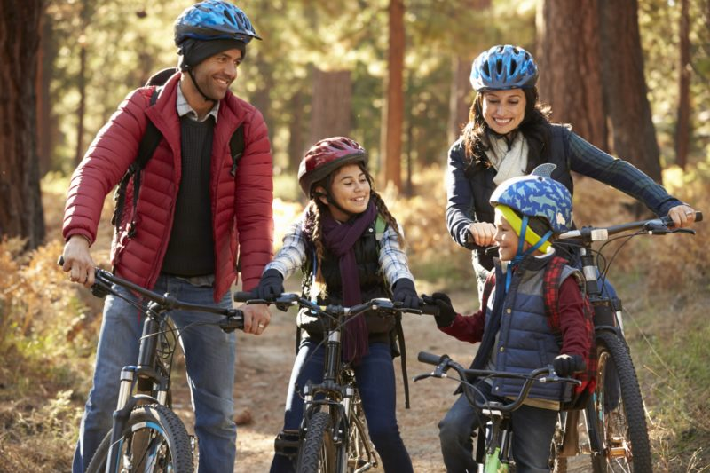 A man, a woman, a boy and a girl sit on bikes, looking toward each other and smiling. Each is wearing a jacket and a helmet. Behind them is a dirt path and several trees.