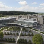 An aerial view of Penn State Health Milton S. Hershey Medical Center and Penn State College of Medicine shows tall buildings, a parking lot with cars in the foreground and hills with trees in the background.