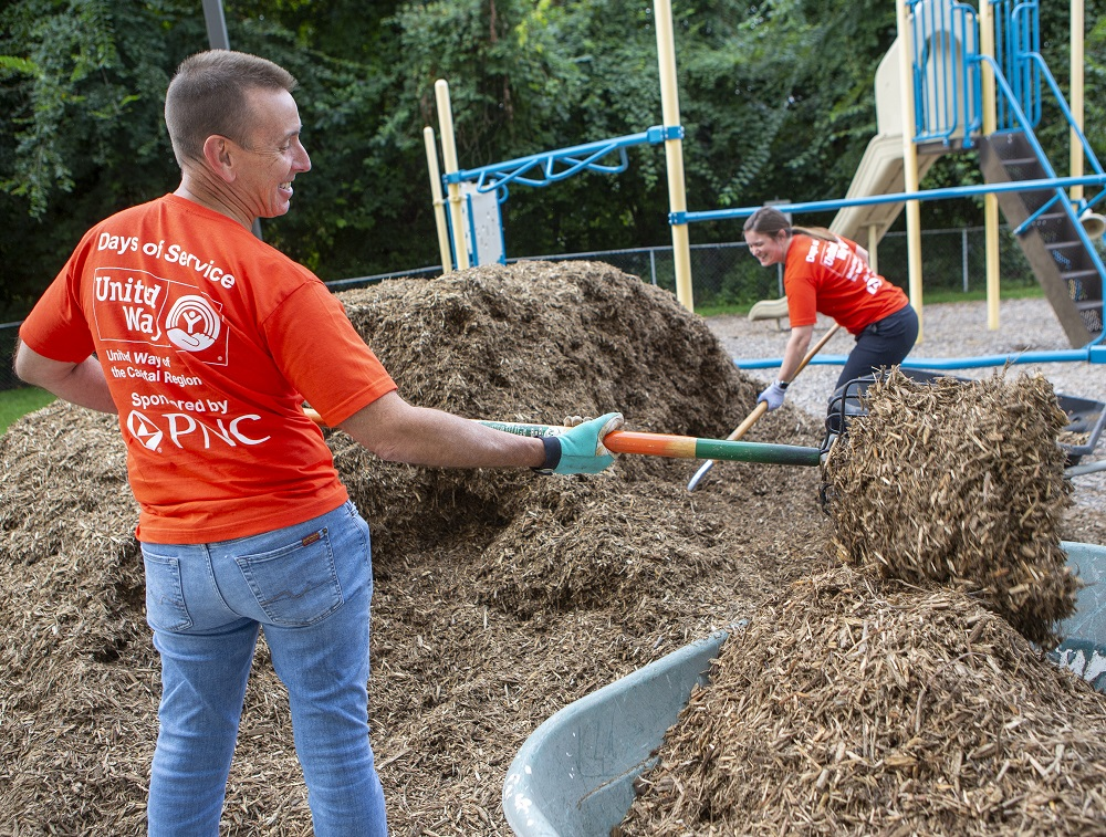 Dr. Kevin Black smiles as a hoists a pitchfork loaded with mulch to a wheel barrow. Nearby, Debora Berini plunges another pitchfork into a pile of mulch. Both wear United Way Days of Service T-shirts.