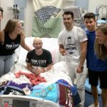 Wearing a Penn State CrossFit shirt and sitting up in a hospital bed, Lily Jordan laughs. Next to her are two women and three young men, the Jonas Brothers.