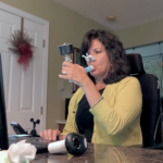 ALS patient Cynthia Lacey holds a spirometer in her mouth. Noseplugs are on her nose. She is looking into a laptop computer. Next to her a man is standing with his hands crossed. Behind her a living room is visible.