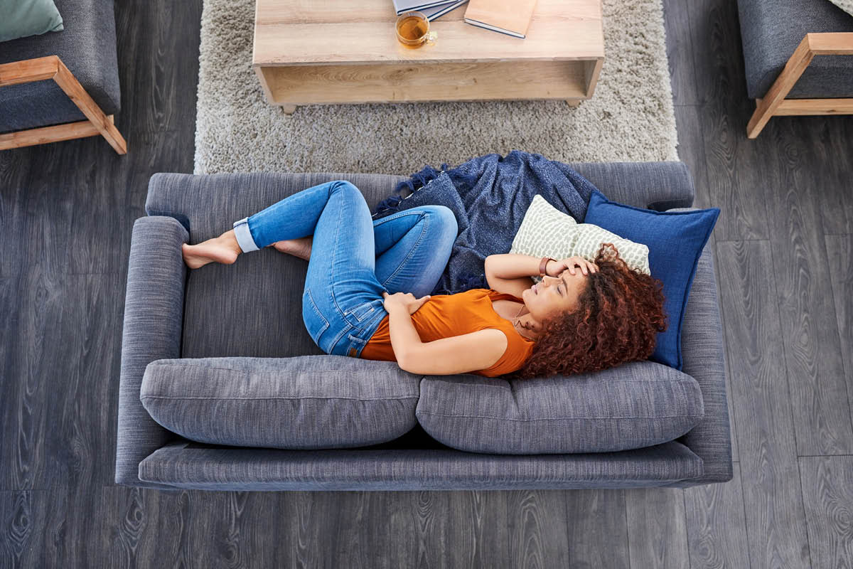 Overhead view of a woman with long hair laying on her right side, body slightly curled up, on a love seat. Her left hand is on her abdomen, her right hand is on her head, in apparent pain.