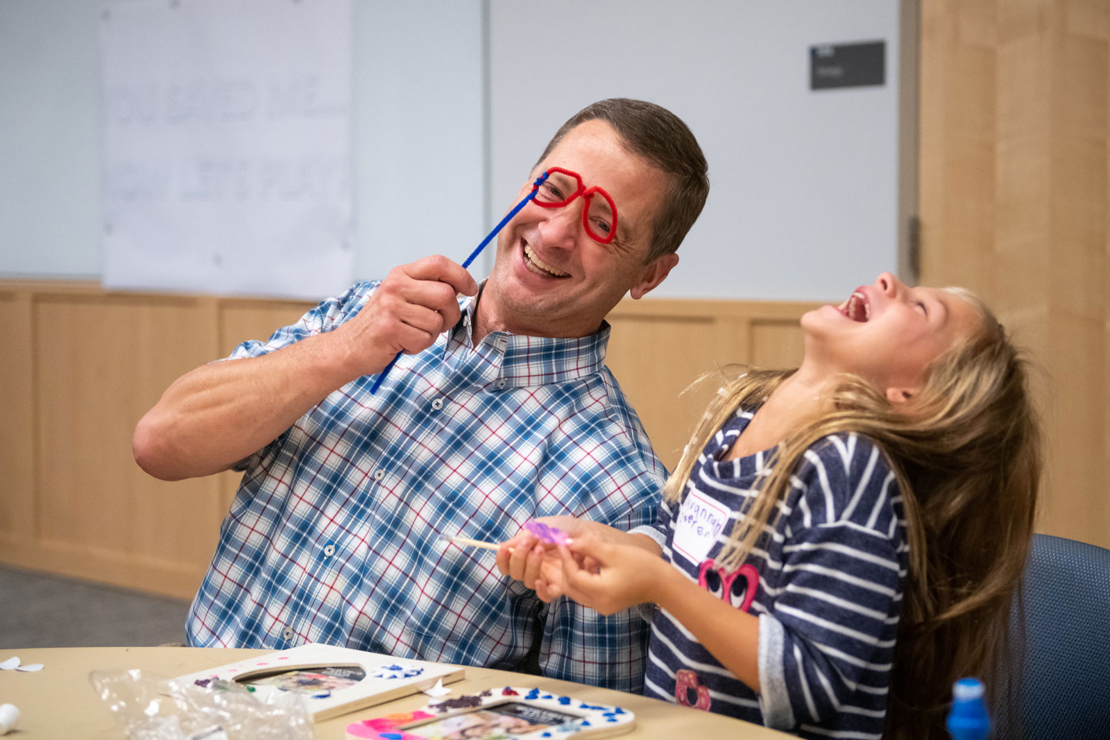 Dr. Christopher O'Hara holds up pipe cleaners twisted into two circles on a straight length of pipe cleaner and leans toward Savannah Doster, who throws back her head and laughs. The two are seated at a table upon which are frames and craft materials.