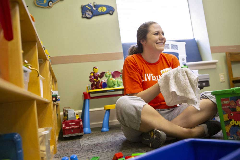 "Mary Lucas, wearing a ""Live United"" T-shirt, sits cross-legged on a carpeted floor. She smiles as she cradles a toy in a washrag. Toys are stacked on shelves and tables around her."