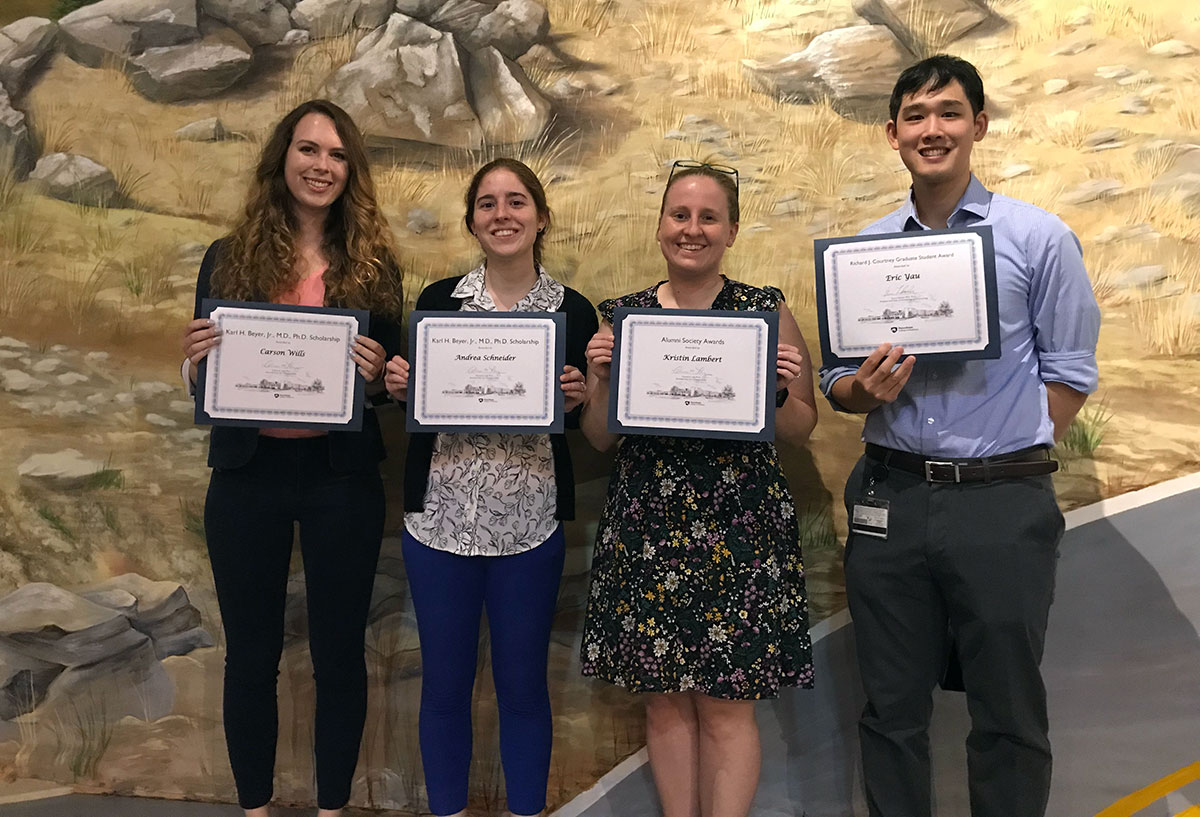 Four students are pictured standing in a row, holding certificates and smiling.