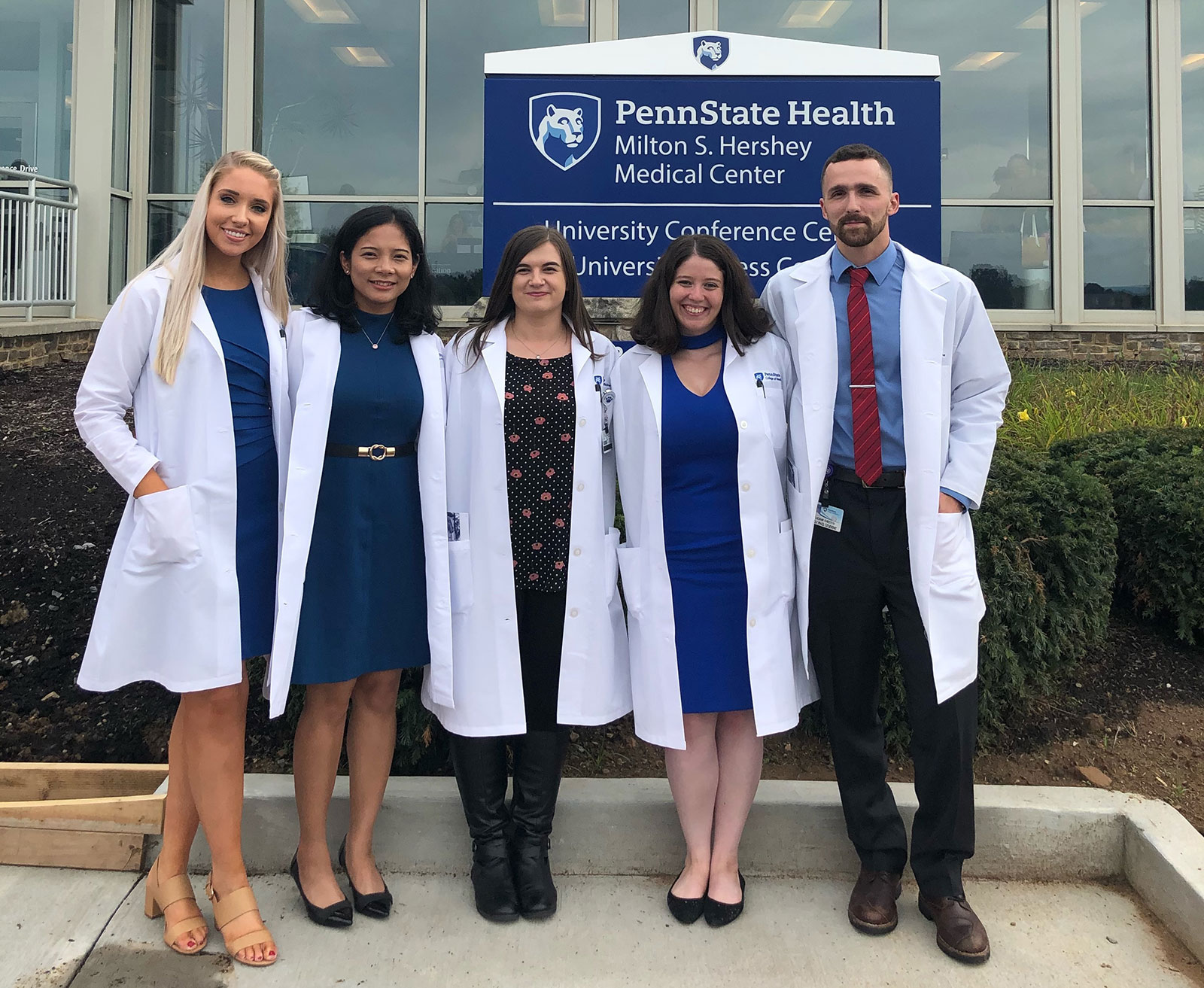 Five graduate students are seen wearing long laboratory coats and dress clothes, standing in front of a Penn State Health conference center in August 2019.